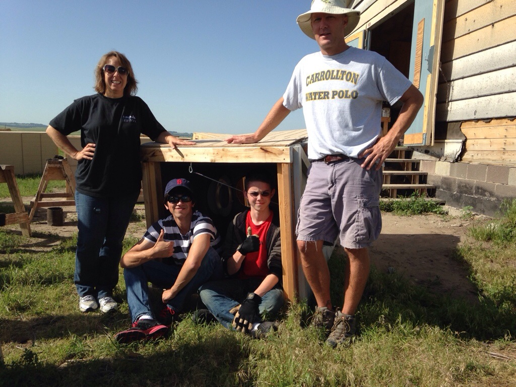 Monta, Allie, Nathan, and Matt picking up the outhouse