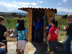 Arturo explains the compostable outhouse.