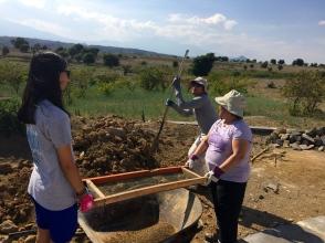 Emily and Dr. Bundang shifting dirt to make a wall.