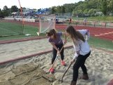 Julia and Cat ready the pit for the long jump.
