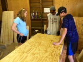 Jaycee with Almedon and another student measuring wood for a project