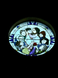 Rose window showing Jesus with Native American children.